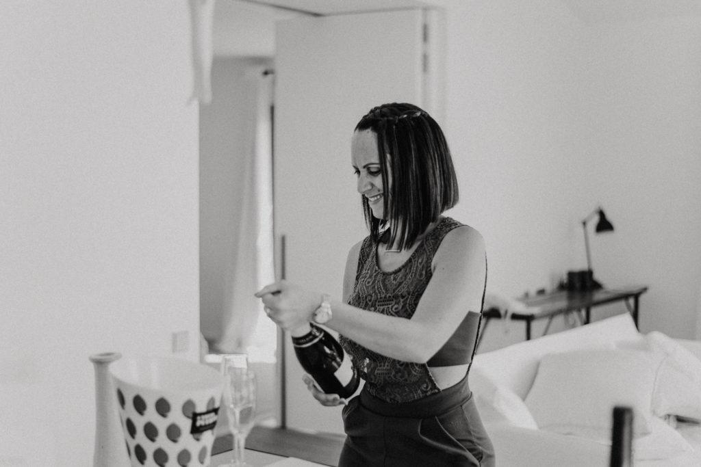 Femme ouvrant une bouteille de champagne