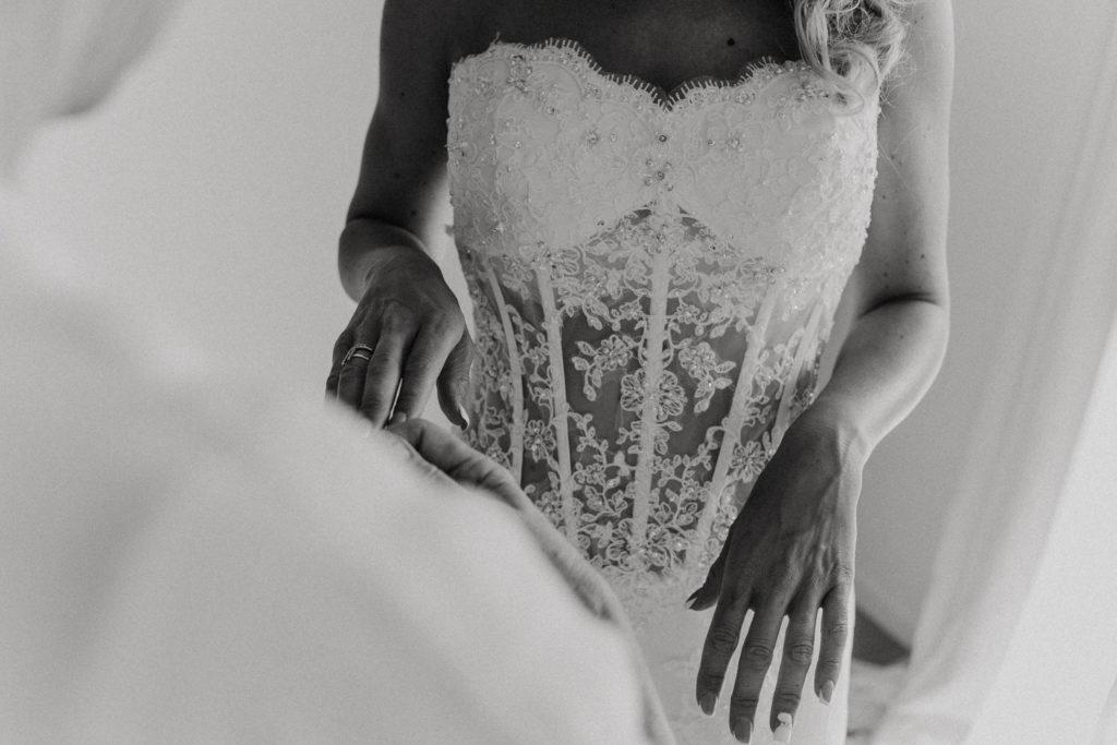 Femme en train de mettre ses gants en dentelle de mariée
