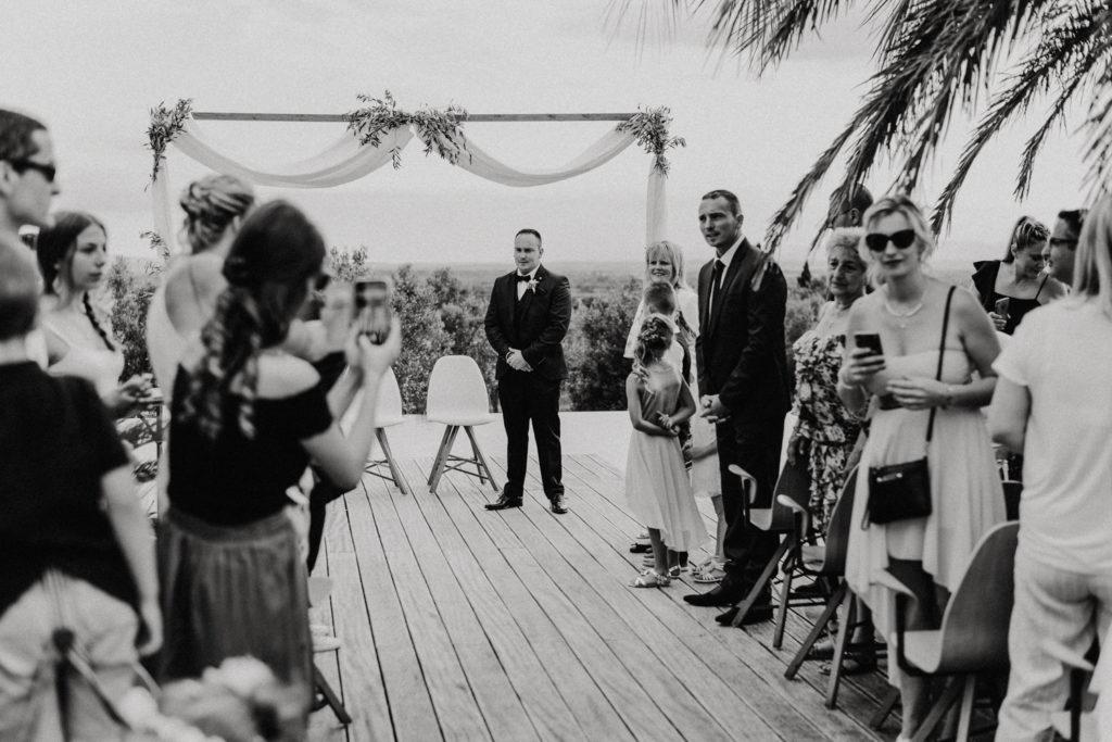 Homme devant l'autel et invités attendant la mariée
