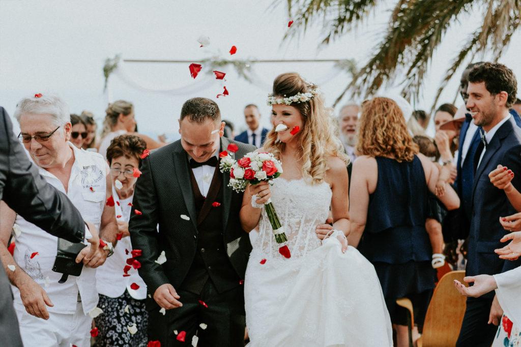 Jeunes mariés recevant des pétales de fleurs