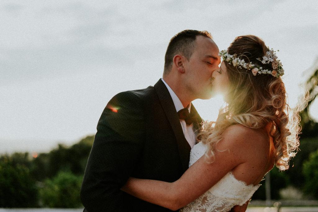 Jeunes mariés s'embrassant au coucher du soleil