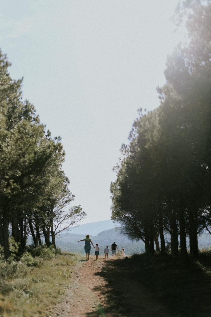 Photographe famille Perpignan - Famille marchant sur un chemin entre des rangés d'arbres