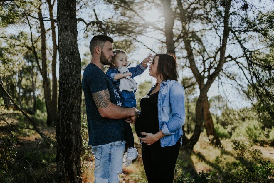 Photographe grossesse olonzac - Petite fille dans les bras de son père et femme enceinte