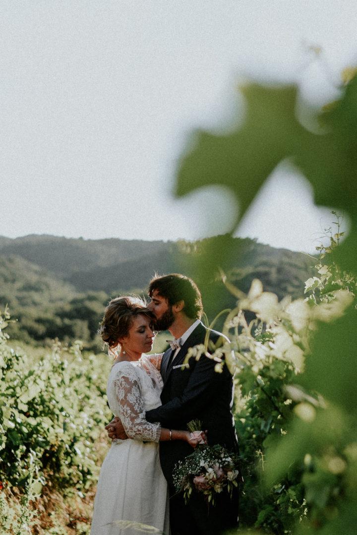 Jeunes mariés s'embrassant dans une vigne au coucher du soleil au Domaine Bellavista à Thuir