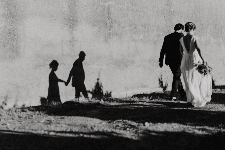 Photographe mariage perpignan - Domaine Bellavista Thuir - Jeunes mariés marchant avec leur ombre sur un mur