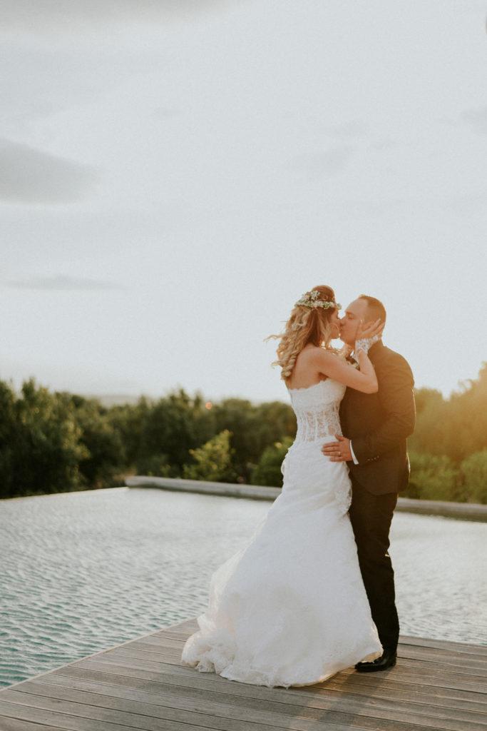Jeunes mariés s'embrassant au bord d'une piscine au coucher du soleil