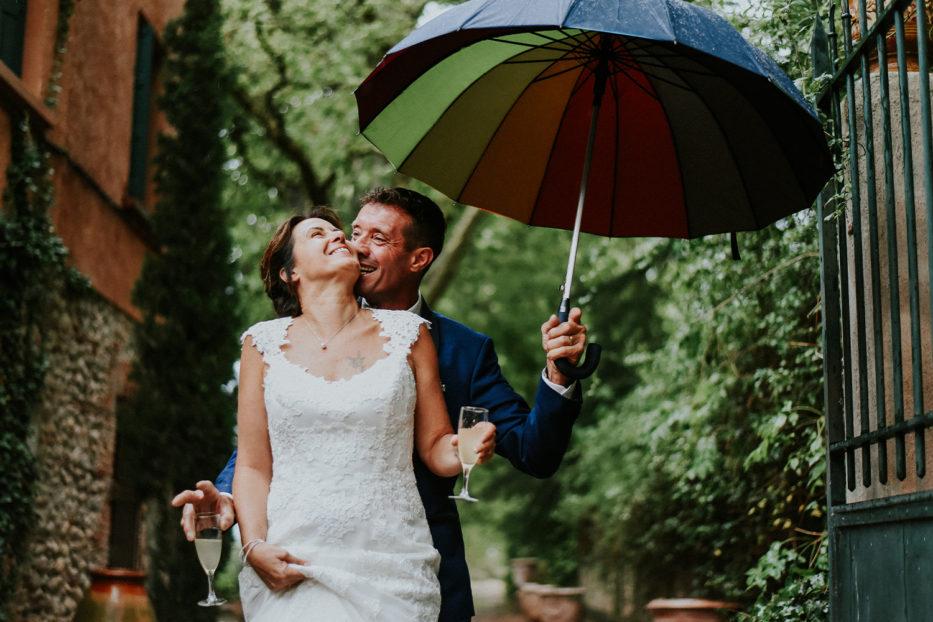 Photographe mariage perpignan - couple pendant le vin d'honneur sous un parapluie - château las collas